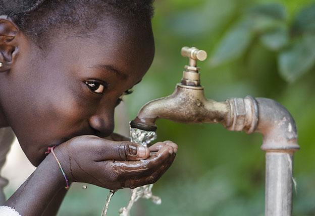 girl drinking water from outdoor faucet
