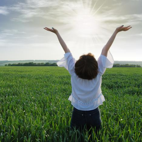 Woman raising her hands in the sun