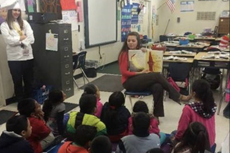 Woman reading a picture book to children in a classroom