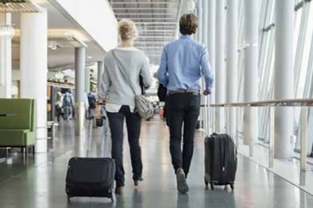 Two airlines passengers roll suitcases down a hall