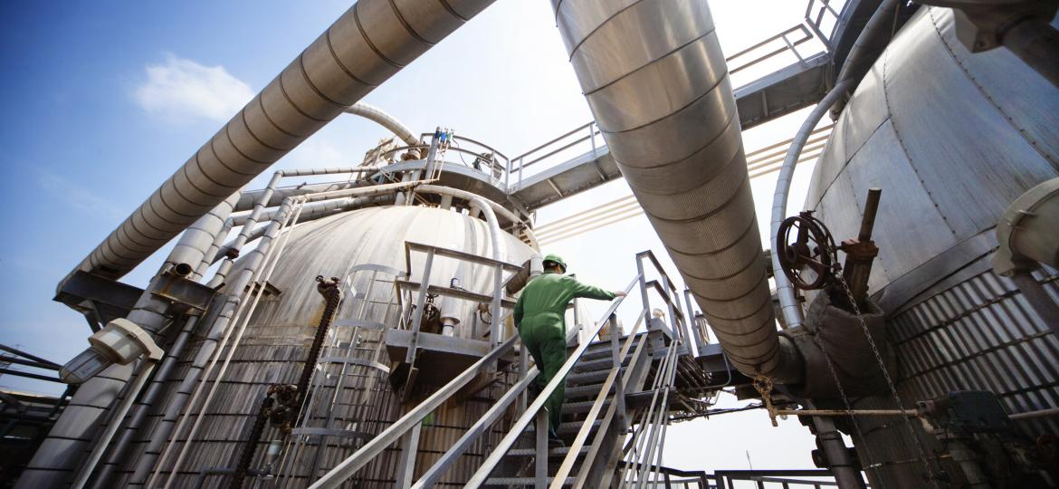 man walking up industrial plant